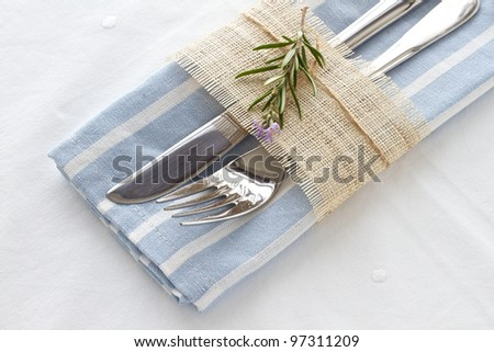 Knife and fork with a blue and white striped napkin and rosemary - stock photo