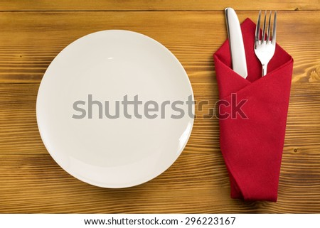 knife and fork with napkin on wooden background - stock photo