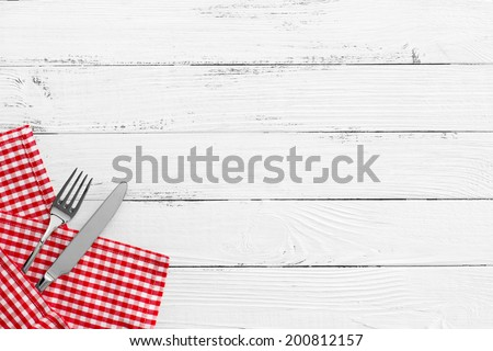 knife and fork with red checked tablecloth and copyspace on white old vintage wooden table - stock photo