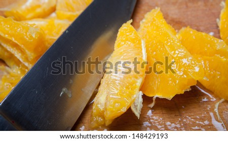 knife chopping oranges into segments on a wooden board. cooking with fruit. - stock photo