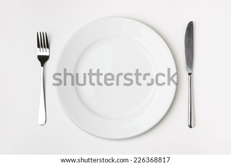 Knife, Fork and plate on table isolated. - stock photo