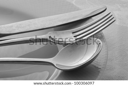 Knife, Fork, Spoon on White Plate in Black and White - stock photo