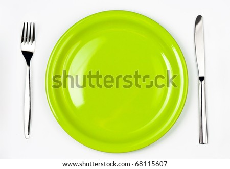Knife, green plate and fork - stock photo