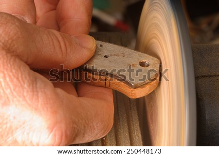 Knife maker sanding a wooden handle/grip to shape - stock photo