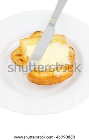 Knife spreading butter on toast in white plate - stock photo