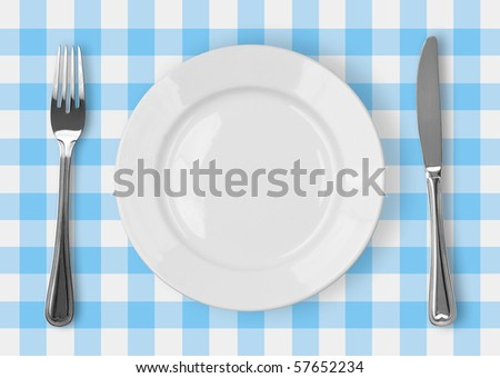 Knife, white plate and fork on blue checked tablecloth - stock photo
