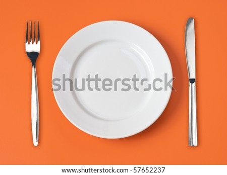 Knife, white plate and fork on orange background - stock photo