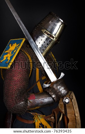 Knight is holding a sword and shield - stock photo