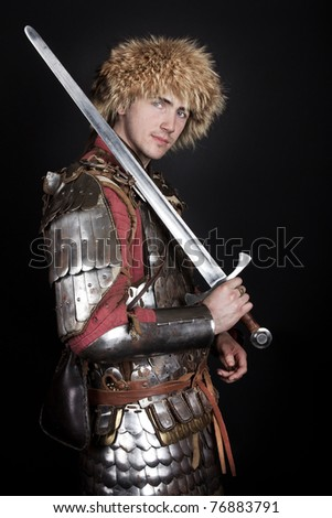 knight is wearing a fur cap and posing - stock photo