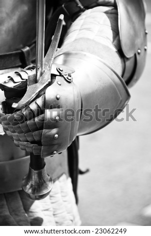 Knight's hand holding a sword, monochrome. - stock photo