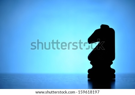 Knight to the rescue - a single wooden chess piece is silhouetted against a backlit blue background with a central highlight and lots of copyspace for your text in this game of strategy and skill - stock photo