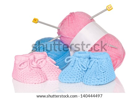 Knitted baby booties with blue and pink wool plus knitting needles, isolated on a white background. - stock photo
