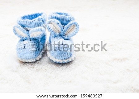 Knitted blue baby booties with rabbit muzzle for little boy - stock photo