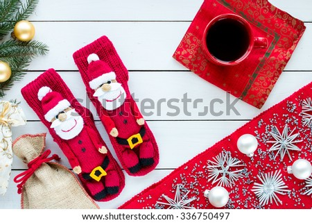 knitted Christmas Stockings as Santa's on white painted wood background with Christmas tree and decorations. Red tablecloth with silver decorations. Red cup of tea. Top view, free space for text. - stock photo