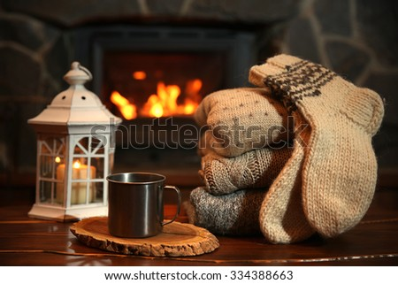 Knitted clothes on table on fireplace background - stock photo
