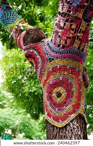 Knitted crochet colorful woolen sweater on a tree trunk - stock photo