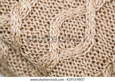 Knitted Norwegian diagonal pattern with front and reverse loop braids from natural cashmere with silk yarn on folded knitted pullover background , close up - stock photo