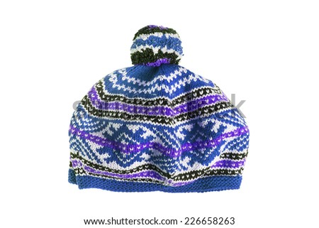 Knitted ornamental blue cap with pompon isolated over white - stock photo