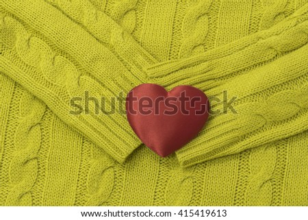 Knitted woolen background and red heart  - stock photo