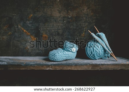 Knitting baby shoes with blue yarn - stock photo