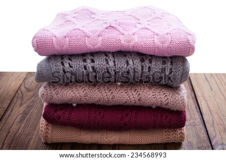 Knitting clothes on wooden background isolated. - stock photo