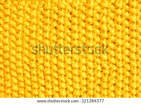 Knitting in moss stitch with yellow wool as an abstract background texture - stock photo