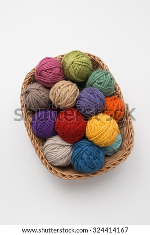 Knitting needles and yarn balls in basket - stock photo