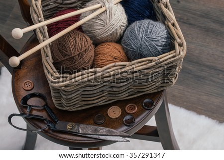 knitting needles, scissors and yarn inside old basket on wooden chair - stock photo