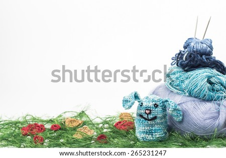 knitting toy rabbit on a background of thread - stock photo