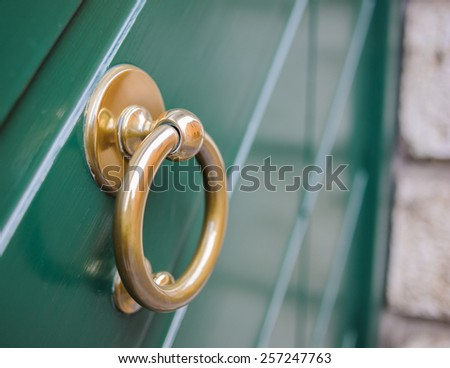 knocker ring of brass on a wooden door colored green - stock photo