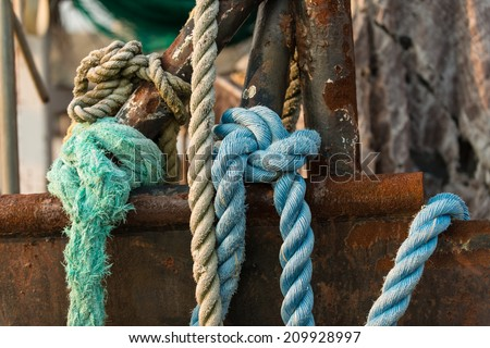 Knotted blue rope laying over the side of a rusting frame and hull of a deep sea trawler - stock photo