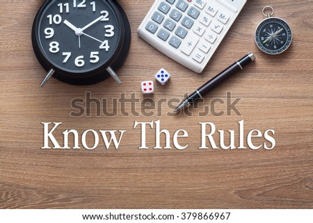 Know the rules words written on wooden table with clock,dice,calculator pen and compass - stock photo