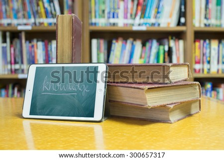 knowledge font in PC tablet and books at library room,education and technology concept - stock photo