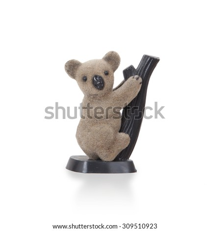 Koala figurine on a branch with white background - stock photo
