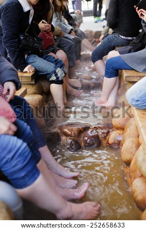 KOBE, JAPAN - FEBRUARY 14, 2015: Tourists enjoy a free foot bath (ashiyu) outside the larger of Arima Onsen's two public bath houses, Kin no Yu. Arima Onsen is one of Japan's three oldest hot springs. - stock photo