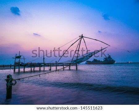 Kochi chinese fishnets and vessel on sunset  in Kerala. Fort Kochin,  South India - stock photo
