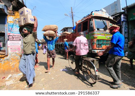 KOCHI, INDIA -FEB 02: Unidentified head load workers unloading gunny bags from a truck in the market on February 02, 2012 in Kochi, India. Head load workers are an organised work force in Kerala. - stock photo