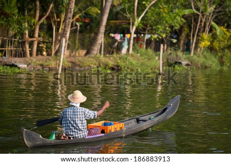 KOCHIN, INDIA-FEBRUARY 23: Hindu on the boat on February 23, 2013 in Kochin, India. Hindu man go by boat suburb of Cochin - stock photo