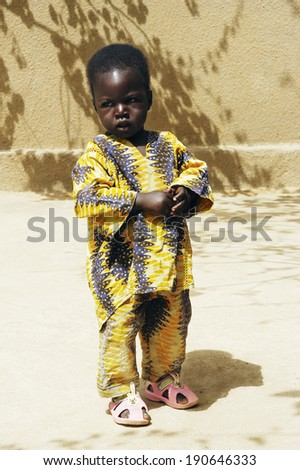 KOKEMNOURE, BURKINA FASO - FEBRUARY 25: a child of the village Kokemnoure dressed in his best suit on the occasion of the celebration organized in the village, february 25, 2007. - stock photo