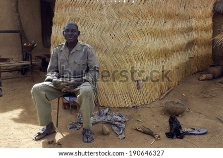 KOKEMNOURE, BURKINA FASO - FEBRUARY 21: Portrait of a man, villager from Kokemnoure in Burkina Faso poses in front of him in front of his house, february 21, 2007. - stock photo
