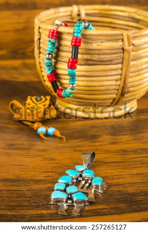 Kokopelli, Traditional Fertility Deity of Southwestern Tribes, in turquoise and silver pendant with more Native American artifacts as background. - stock photo