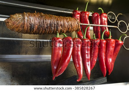 Kokorec And Some Sweet Red Peppers On A Skewer. Kokorec is a traditional Turkish street food made of lamb intestine. - stock photo