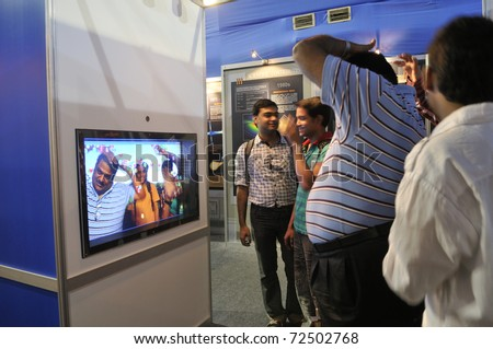 KOLKATA- FEBRUARY 20:  Visitors watching themselves in a bubble screen,during the Information and Communication Technology (ICT) conference and exhibition on February 20, 2011 in Kolkata, India. - stock photo