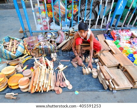 Kolkata, India - April 13, 2016: A child selling kitchen items made of wood in the street. - stock photo