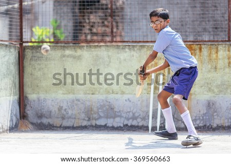 KOLKATA, INDIA   APRIL 14, 2013: Poor indian boy concentrates on a ball playing cricket in the children school    - stock photo