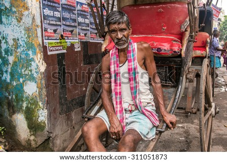 KOLKATA, INDIA - AUGUST 22: An Indian Rickshaw puller waits for passengers on August 22, 2015 at College Street in Kolkata, West Bengal, India. - stock photo