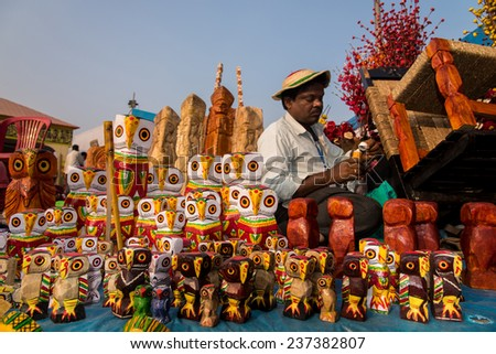 KOLKATA, INDIA - DECEMBER 7: An Indian craftsman creates colorful handicraft toys for sale during the annual State Handicrafts Expo 2014 on December 7, 2014 in Kolkata, West Bengal, India. - stock photo