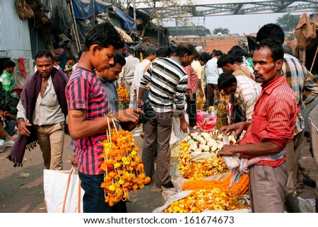 KOLKATA, INDIA - JAN 13: Customers communicate with the traders of crowded flower market on January 13, 2012 in Calcutta. Only 0.81% of the Kolkata's workforce employed in primary sector (agriculture) - stock photo
