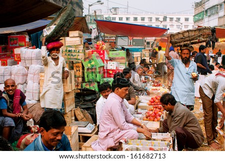 KOLKATA, INDIA - JAN 13: Fruits traders sell apples and oranges on the street market on January 13, 2012 in Calcutta. Only 0.81% of the Kolkata's workforce employed in the primary sector (agriculture) - stock photo