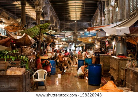 KOLKATA, INDIA - JAN 10: Workers and traders of the old city market clean counters and wash the floor on January 10, 2012 in Calcutta. Only 0.81% of Kolkata's workforce employed in agriculture - stock photo